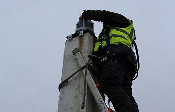 Man on a ladder carrying out JFC Marine Installation & Servicing