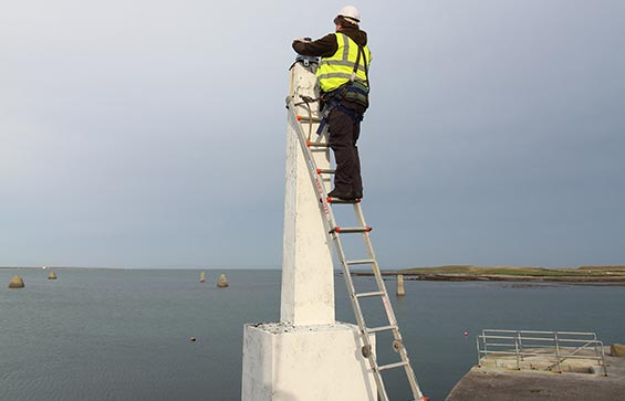 Man on ladder carrying out JFC Marine Lantern Tower Maintenance & Servicing
